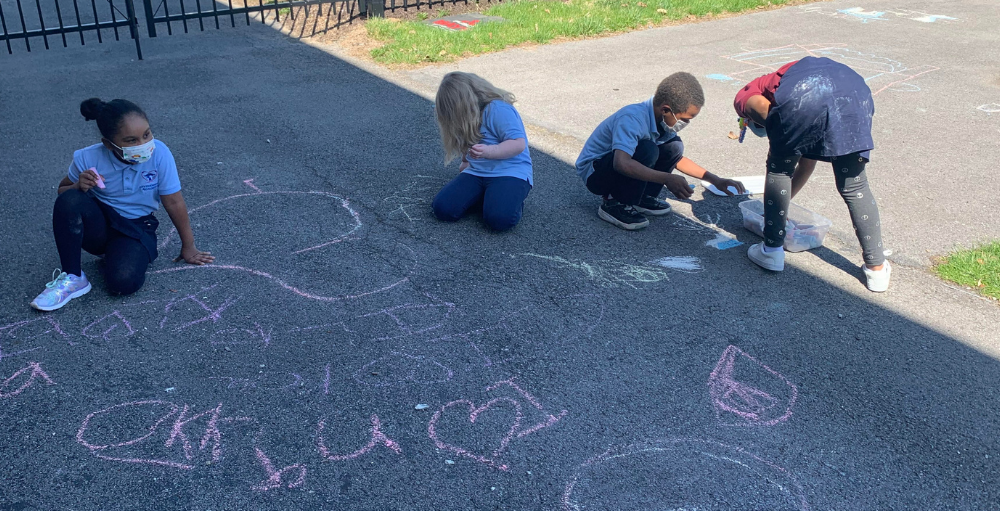 Students express their creativity with sidewalk chalk during their outdoor recess.